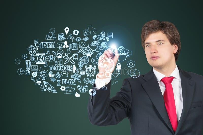 Vista frontale di un uomo d'affari in legame rosso che disegna uno schizzo su vetro immagine stock libera da diritti