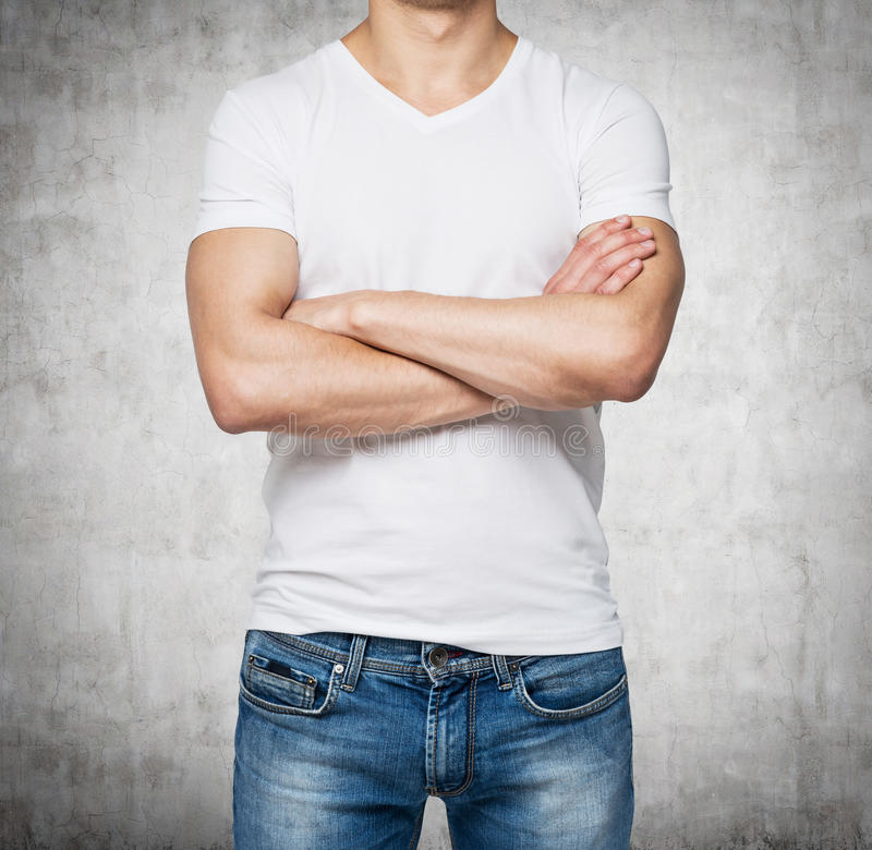 Vista frontale di una persona in una maglietta bianca di forma di v con le mani attraversate immagini stock libere da diritti