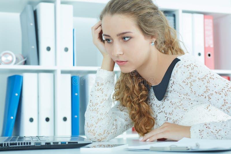 Vista frontale giovane di una donna riccia stanca o annoiata che si siede alla scrivania davanti al computer portatile immagine stock libera da diritti