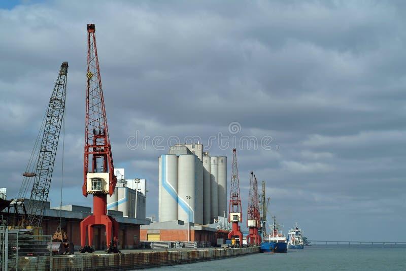 Vista geral da porta com navios e guindastes imagens de stock royalty free