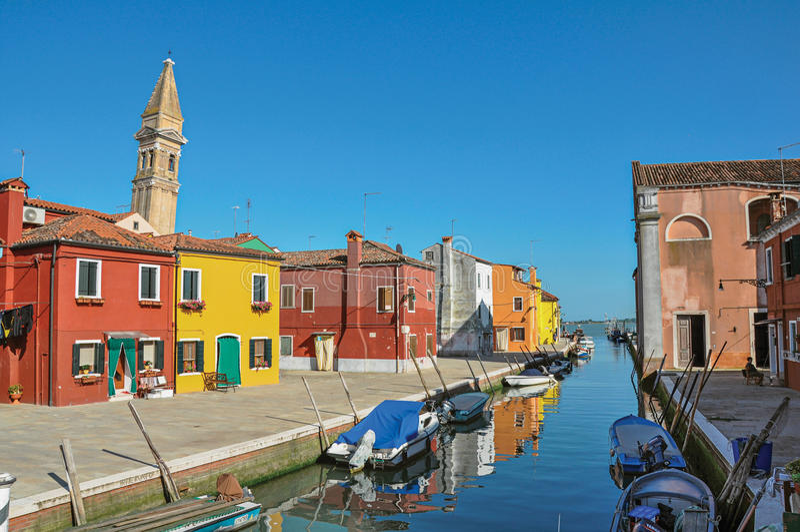 Vista geral das construções, da torre de sino colorida e dos barcos enfrentando um canal em Burano foto de stock royalty free
