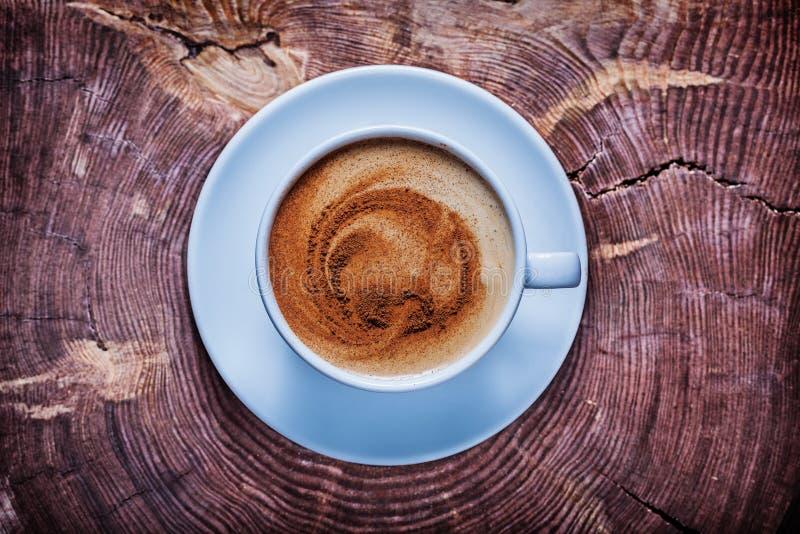 Vista geral de cima do café com espuma e da canela no copo cerâmico branco no tronco de árvore de seção transversal do vintage imagem de stock