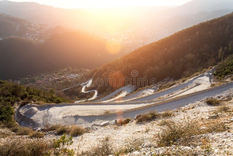 Vista granangular de la carretera con curvas, puesta al top de la montaña Brillo de la puesta del sol fotografía de archivo