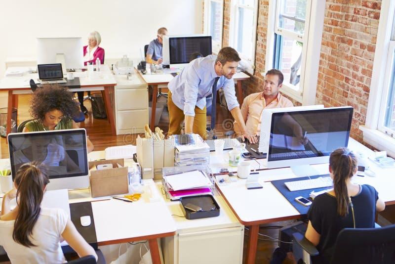 Vista granangular de la oficina conceptora ocupada con los trabajadores en los escritorios imagen de archivo