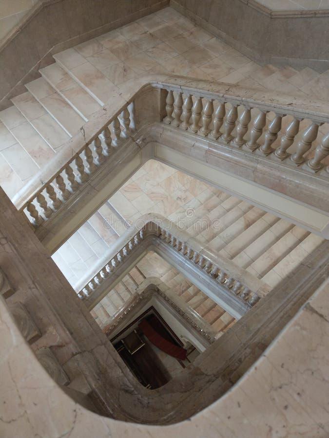 Vista hacia abajo de escaleras de mármol ajustadas con la barandilla de mármol, encendida naturalmente fotografía de archivo libre de regalías