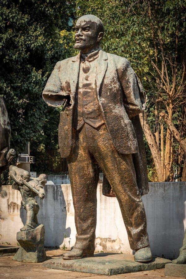 Vista honesto próxima de uma estátua de bronze quebrada vestida de Lenin em um parque da cidade em Tirana Albânia foto de stock