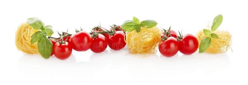 Vista horizontal longa panorâmico larga dos tomates, da massa e da manjericão no branco imagem de stock