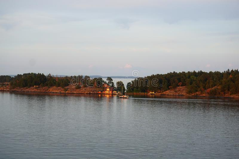 Vista idilliaca della campagna con estate della casa e del lago fotografie stock