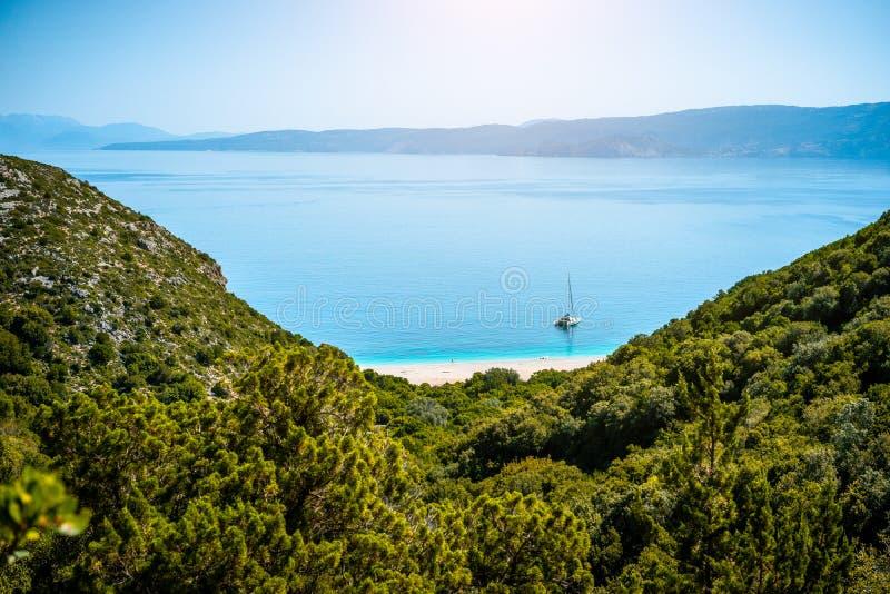 Vista imponente de la playa de Fteri con el velero blanco en la bahía ocultada, Kefalonia, Grecia Rodeado por mediterráneo foto de archivo libre de regalías