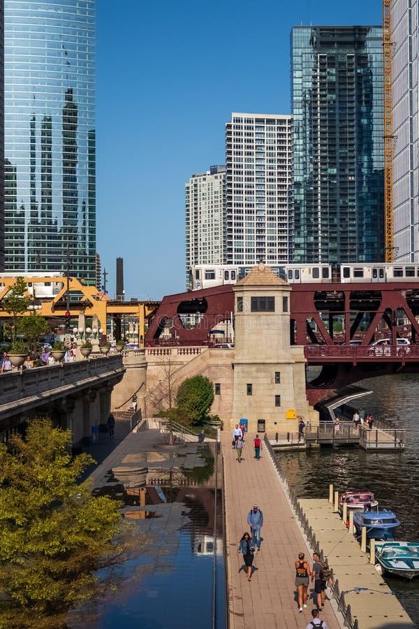 Vista imponente y colorida de dos trenes del EL que cruzan el río Chicago y al Dr. de Wacker mientras que los viajeros caminan en imagenes de archivo