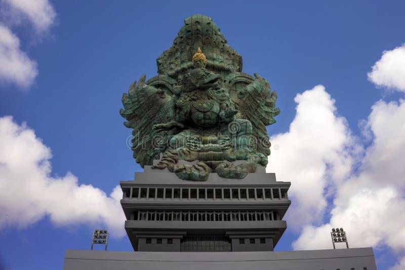 Vista impressionante della statua di rame verde di Garuda Wisnu ispirata nel mito indù che sta maestoso sotto un cielo blu nel vi fotografia stock libera da diritti