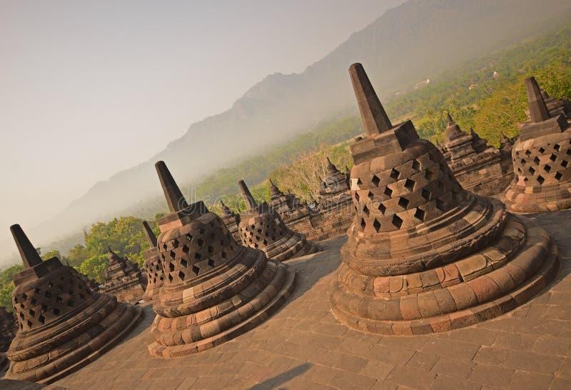 Vista inclinada del gigante Stupas de Borobudur durante última salida del sol con la sensación brumosa entre el bosque en el fond imagenes de archivo