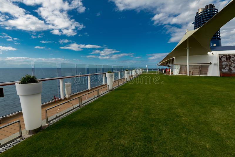 Vista inclinada do gramado verde e dos potenciômetros brancos a bordo do cruzeiro do eclipse da celebridade fotografia de stock royalty free