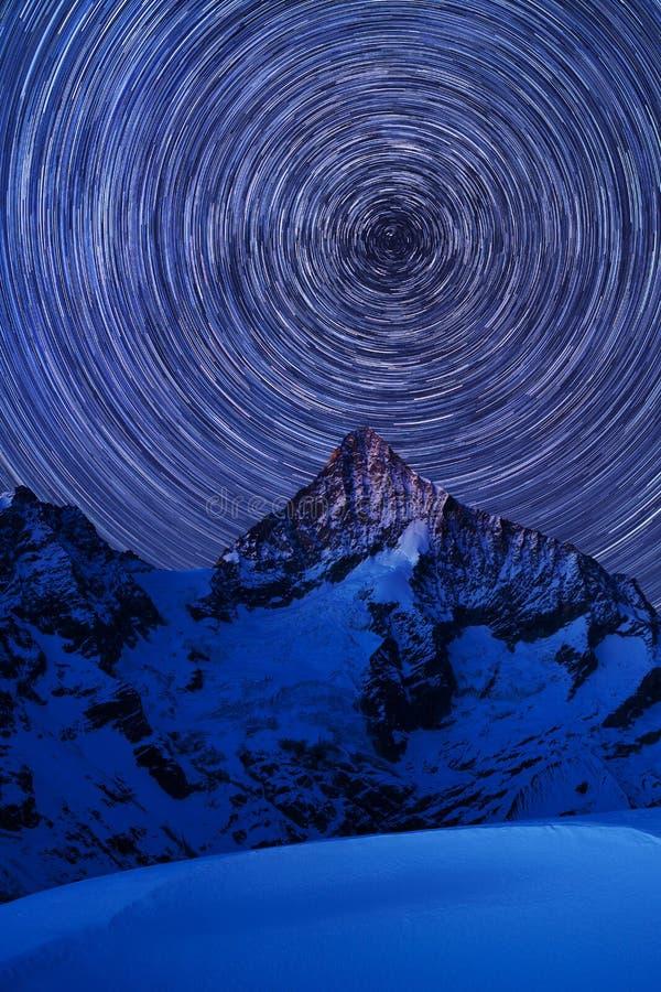 Vista incredibile di notte in alpi svizzere Tracce della stella che si muovono in cielo blu Posizione della località di soggiorno fotografie stock libere da diritti