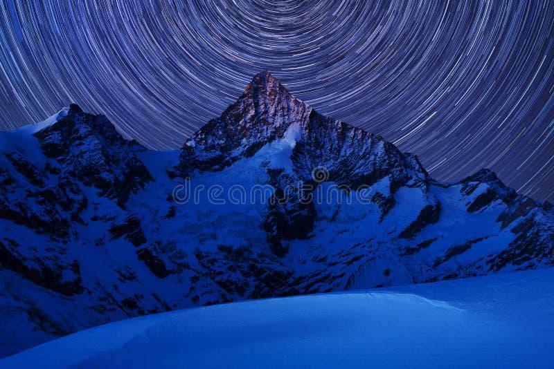 Vista incredibile di notte in alpi svizzere Tracce della stella che si muovono in cielo blu Posizione della località di soggiorno fotografie stock