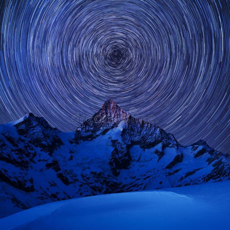 Vista incredibile di notte in alpi svizzere Tracce della stella che si muovono in cielo blu Posizione della località di soggiorno immagine stock libera da diritti