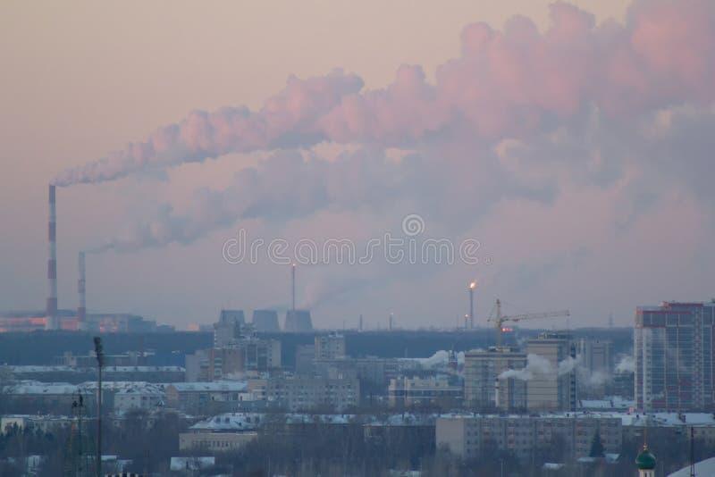 Vista industrial com as tubulações de fumo no por do sol do inverno, conceito da química fotografia de stock