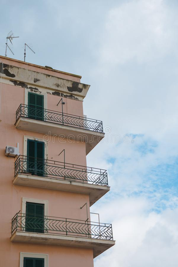 vista inferior de balcones del edificio viejo delante del cielo nublado, fotografía de archivo libre de regalías