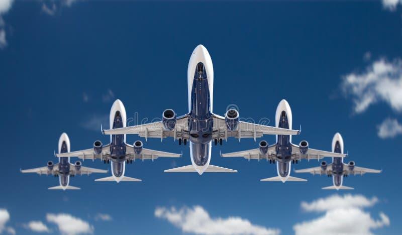 Vista inferior de cinco aviões do passageiro que voam na formação no céu imagem de stock