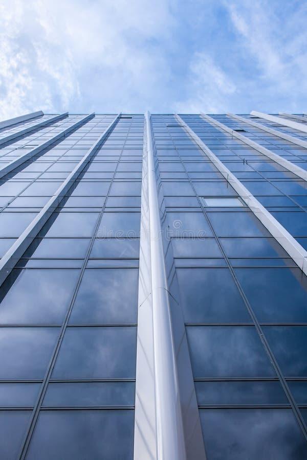 Vista inferior de la fachada del edificio de cristal moderno y del cielo azul nublado encima de ella Opinión de perspectiva imágenes de archivo libres de regalías