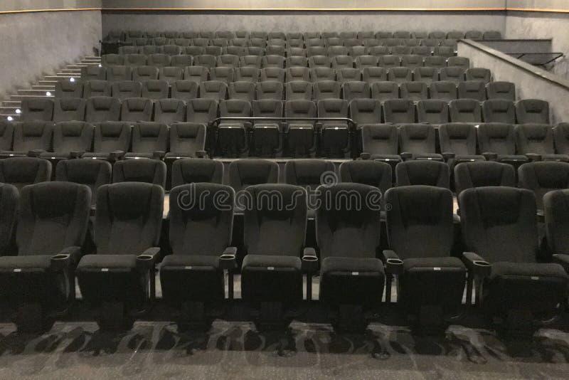 Vista inferior de la manera al pasillo del cine con las sillas suaves negras fotos de archivo