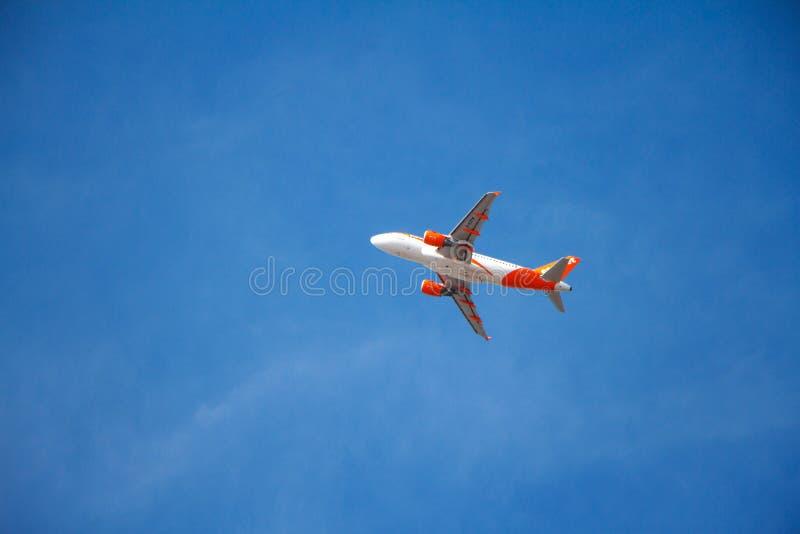 Vista inferior de un vuelo comercial del aeroplano en un cielo azul despejado fotografía de archivo