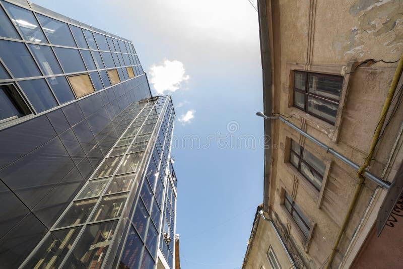 Vista inferior del edificio alto con la pared de cristal enfrente de descuidado crackled enyesado en fondo del espacio de la copi foto de archivo libre de regalías