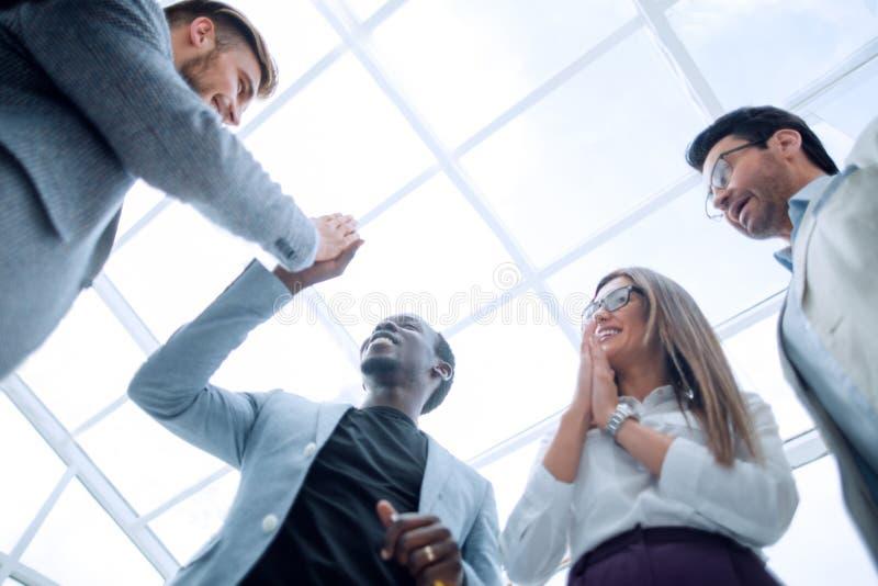 Vista inferior empregados felizes que dão-se uns cinco altos foto de stock
