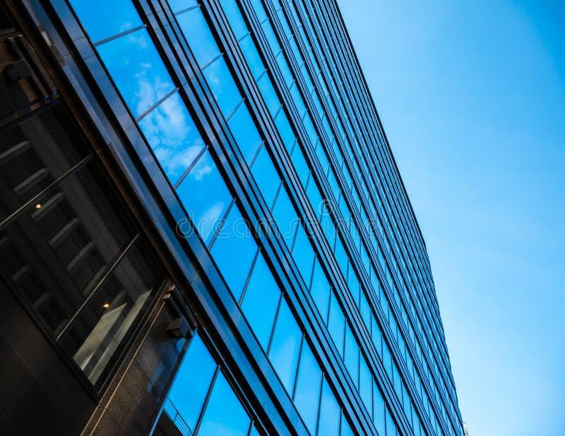 Vista inferior na parede de vidro em arranha-céus modernos da arquitetura no distrito do centro de negócios contra o céu azul imagens de stock royalty free