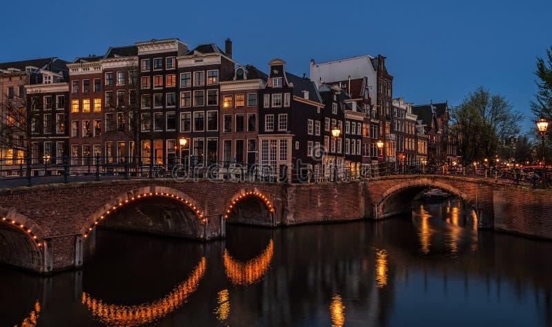 Vista iniziale di notte della molla di paesaggio urbano del amterdam con il ponte del canale e le case medievali nella penombra d fotografia stock