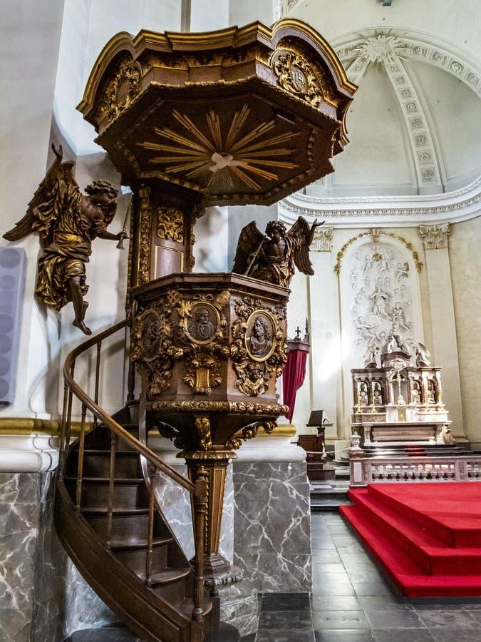 Vista interior de la catedral de Malmedy, Bélgica, el púlpito de madera hermoso a partir de 1770 en el primero plano, el coro en  foto de archivo libre de regalías