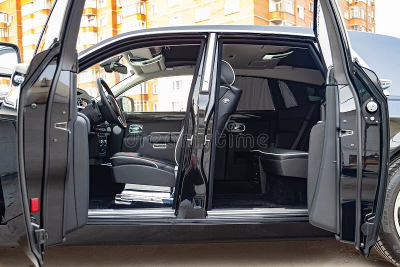 Vista interior de novo um carro muito caro, uma limusina preta longa com portas abertas, painel, volante, assentos no estacioname fotos de stock