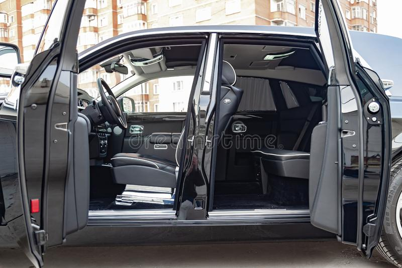 Vista interior de novo um carro muito caro, uma limusina preta longa com portas abertas, painel, volante, assentos no estacioname imagem de stock royalty free