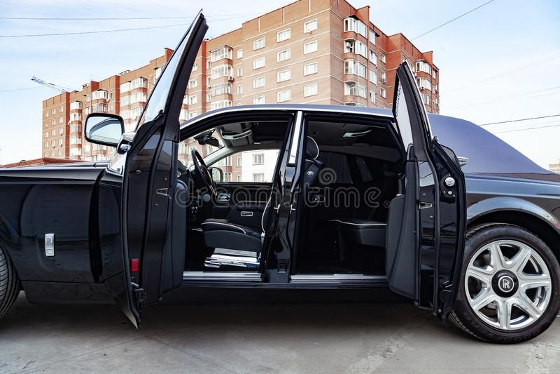 Vista interior de novo um carro muito caro, uma limusina preta longa com portas abertas, painel, volante, assentos no estacioname fotografia de stock