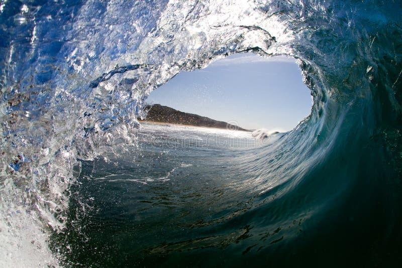 Vista interior de una onda de fractura en una playa tropical debajo de un cielo azul fotos de archivo libres de regalías