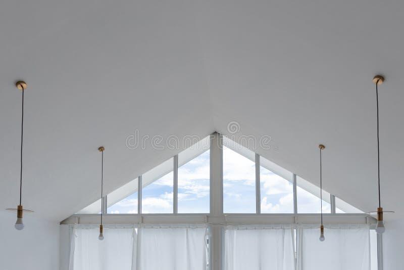 Vista interna della finestra di forma del triangolo con il cielo bianco della nuvola e della tenda fotografia stock libera da diritti
