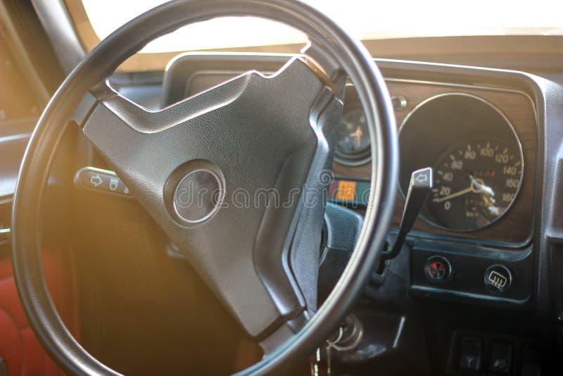 Vista interna di vecchia automobile d'annata rotella interna del trasporto della direzione dell'automobile immagine stock