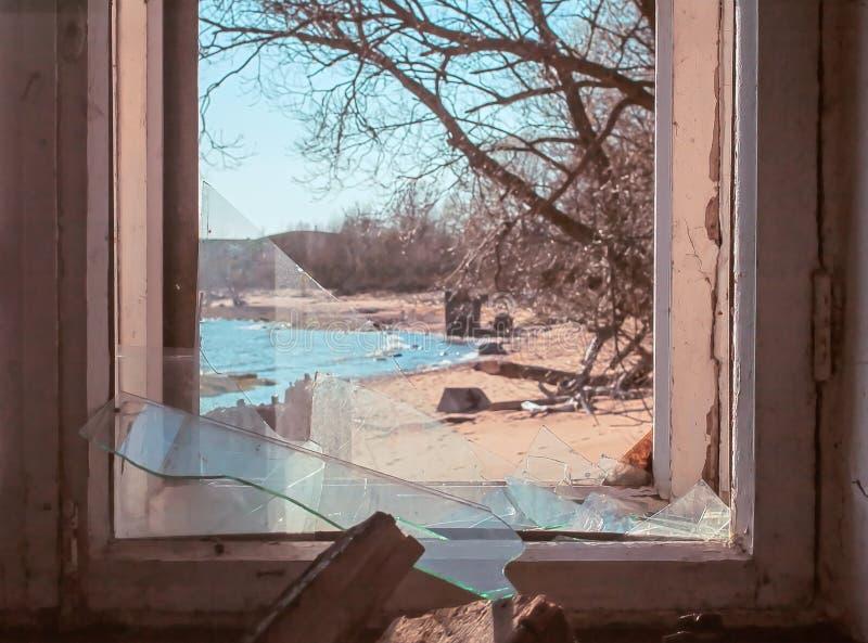 Vista interna Finestra rotta di vecchia costruzione da cui potete vedere la spiaggia con la baia immagine stock