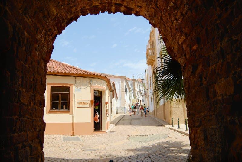 Vista a la calle con el canal histórico de los edificios un arco en Silves, Portugal foto de archivo libre de regalías