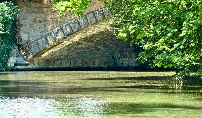 Vista a la esquina de un puente arqueado, desde el agua de un río, con ramas colgantes con hojas en primer plano imágenes de archivo libres de regalías