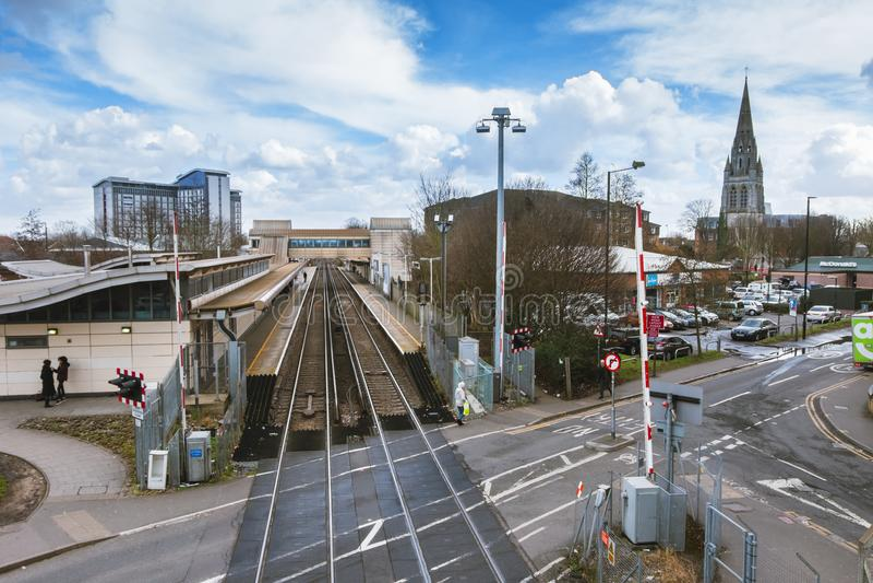 Vista larga da estação de trem de Feltham e da torre da igreja agora-demulida do ` s do St Catherine foto de stock