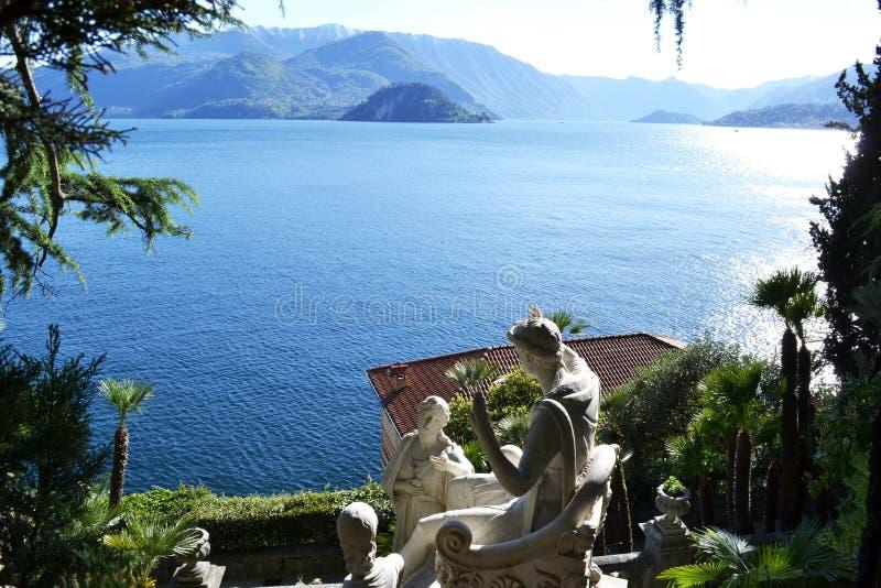 Vista a las esculturas antiguas de Giovan Battista Comolli del chalet Monastero y vista panorámica al lago Como y Bellagio imagen de archivo libre de regalías