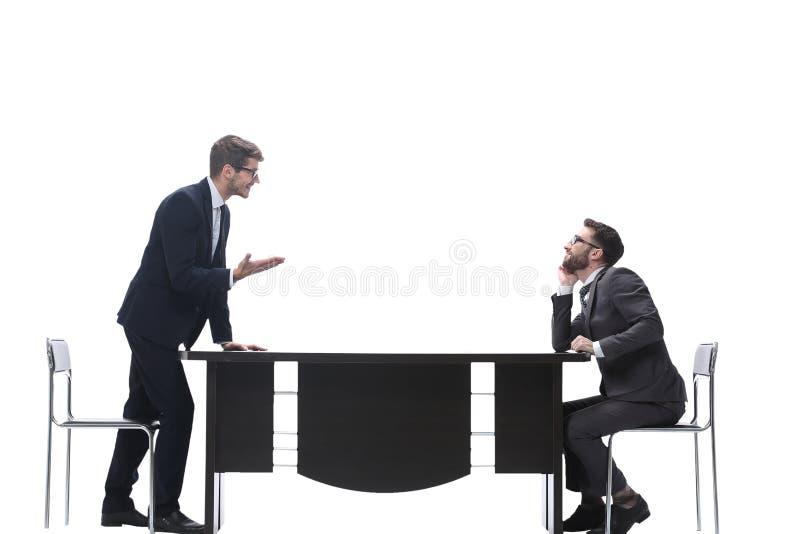 Vista lateral colegas do negócio que discutem algo perto do desktop fotografia de stock