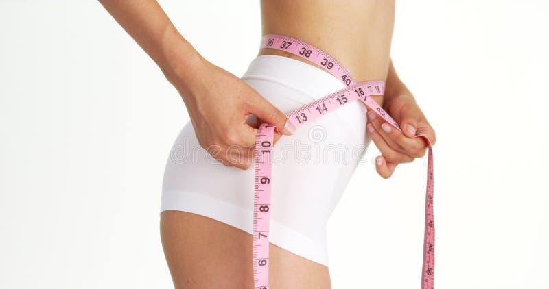 Vista lateral da cintura de medição da mulher delgada imagem de stock