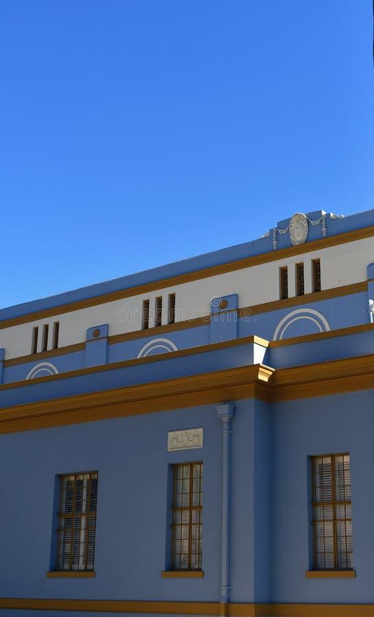 Vista lateral da construção alta com as janelas retangulares que refletem o céu azul brilhante foto de stock