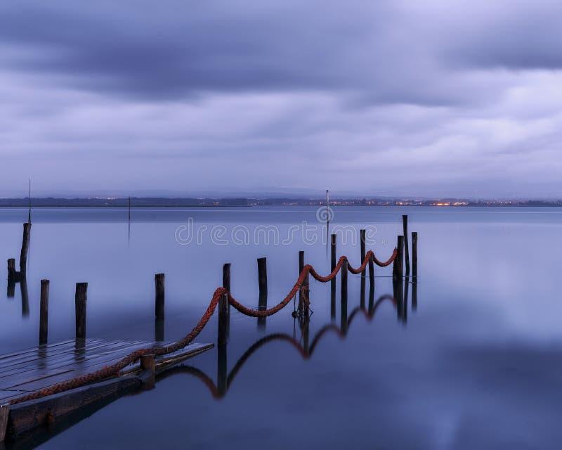 Vista lateral da doca para desaparecer nas águas refletindo do lago imagem de stock royalty free