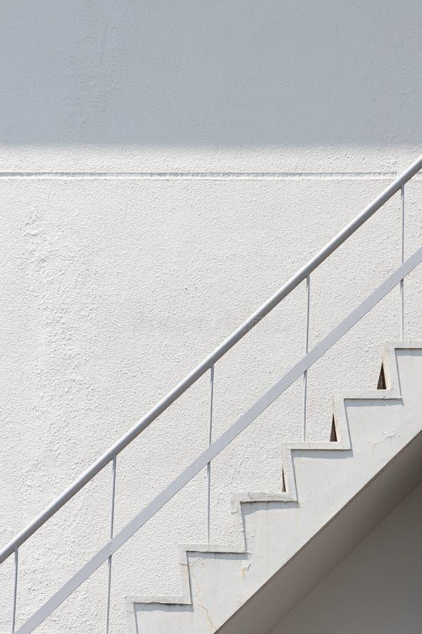Vista lateral da escadaria exterior branca da emergência do escape de fogo com os trilhos e o muro de cimento do corrimão do meta imagem de stock royalty free