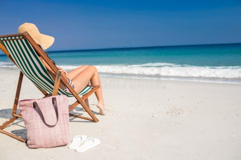 Vista lateral da morena bonita que relaxa na cadeira de plataforma na praia fotografia de stock royalty free