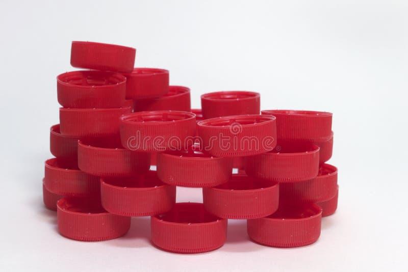Vista lateral da pilha de tampões de garrafa plásticos com nervuras vermelhos, dobrada imagem de stock royalty free