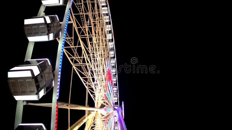 Vista lateral da roda de Ferris enorme que gira no parque de diversões sob o céu noturno escuro fotografia de stock